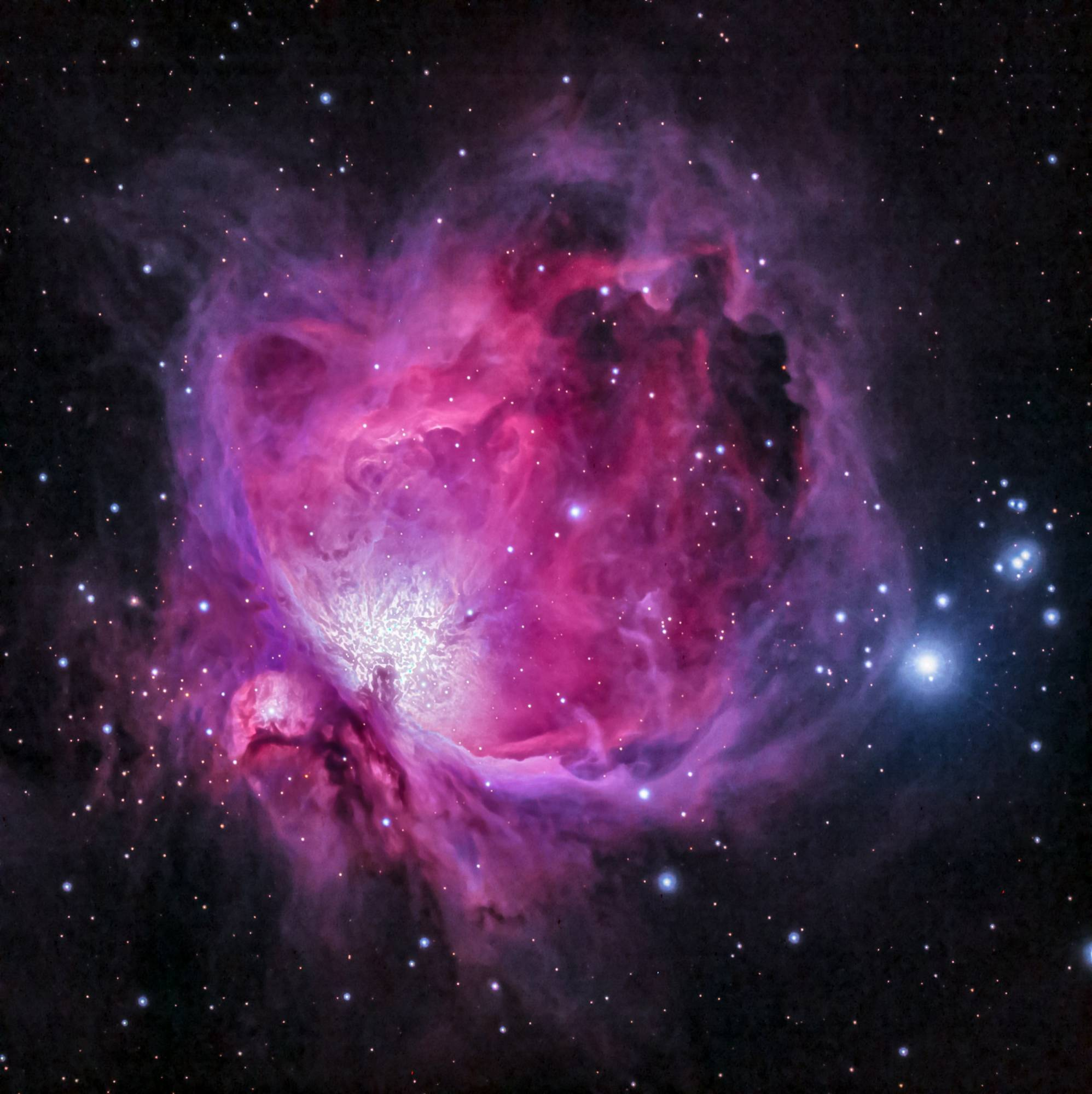 An image of a pink, purple galaxy with bright white stars. Black sky background.