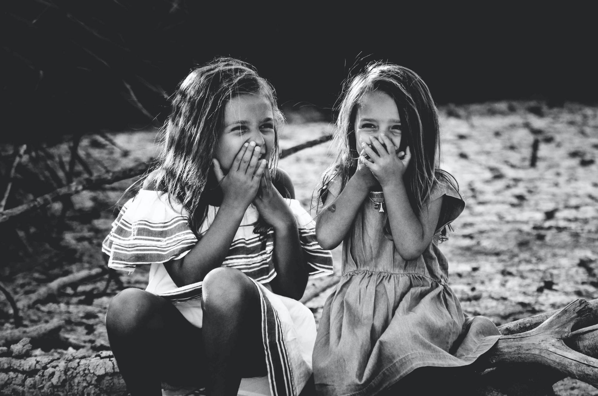 A black and white photo of two young girls laughing.