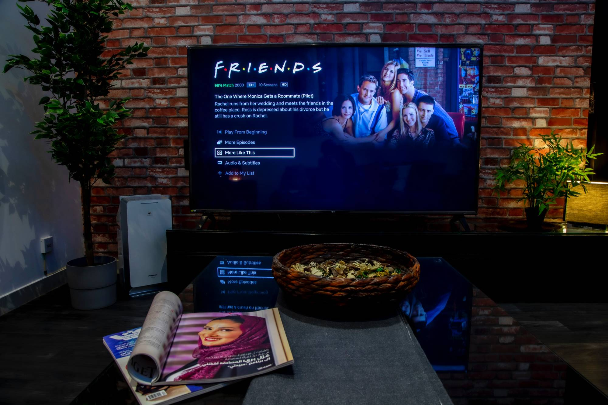 """A black flat screen TV turned on to """"Friends"""" in a living room"""