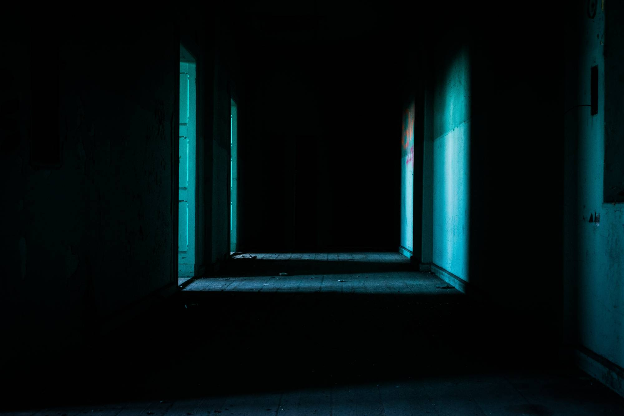 A dark corridor with two open doors on left reflecting blue light on white walls.