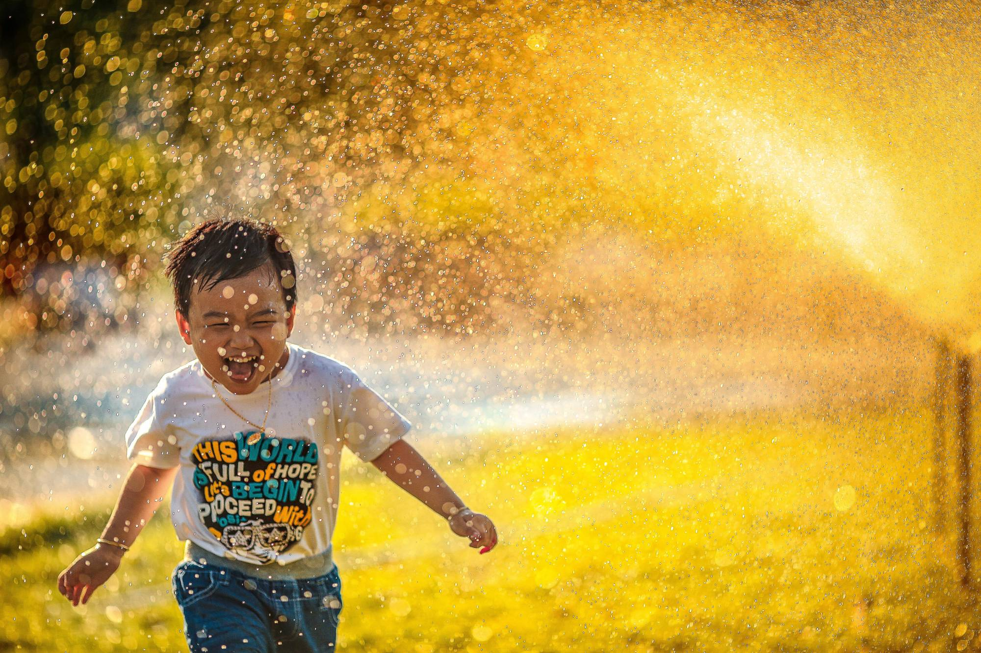 Photo of a small boy running past a water sprinkler