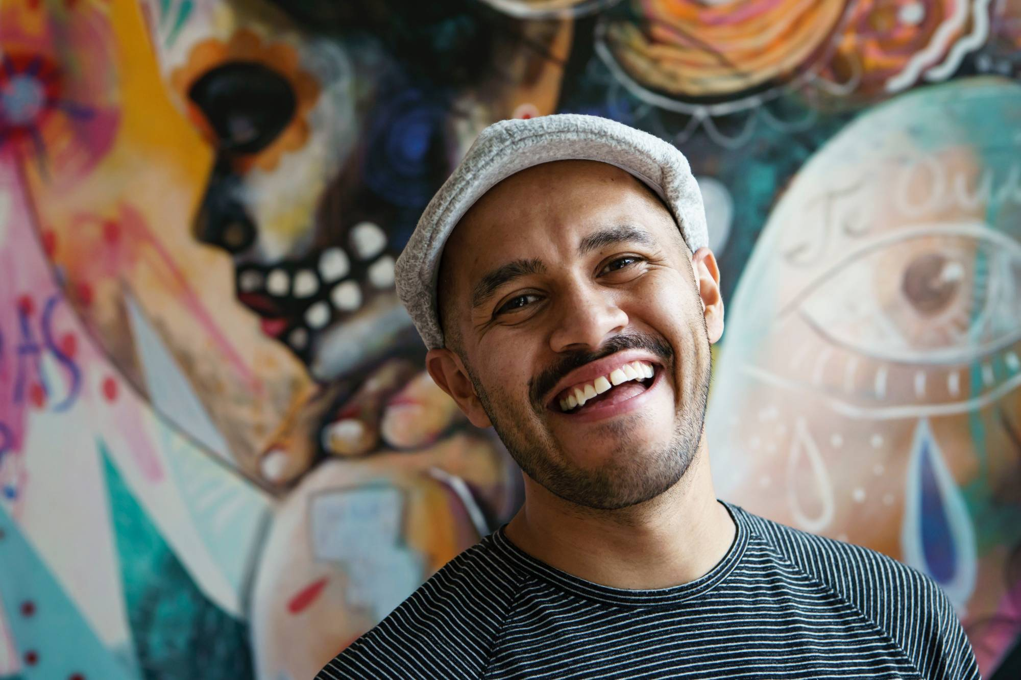 A photo of muralist and performer Armando Silva. Background is a colorful mural.
