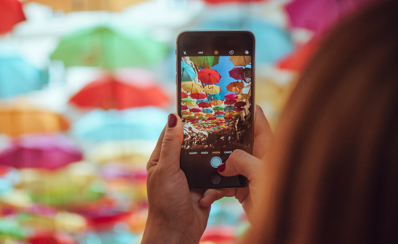 Photo of a person taking a photo of umbrellas using their mobile phone