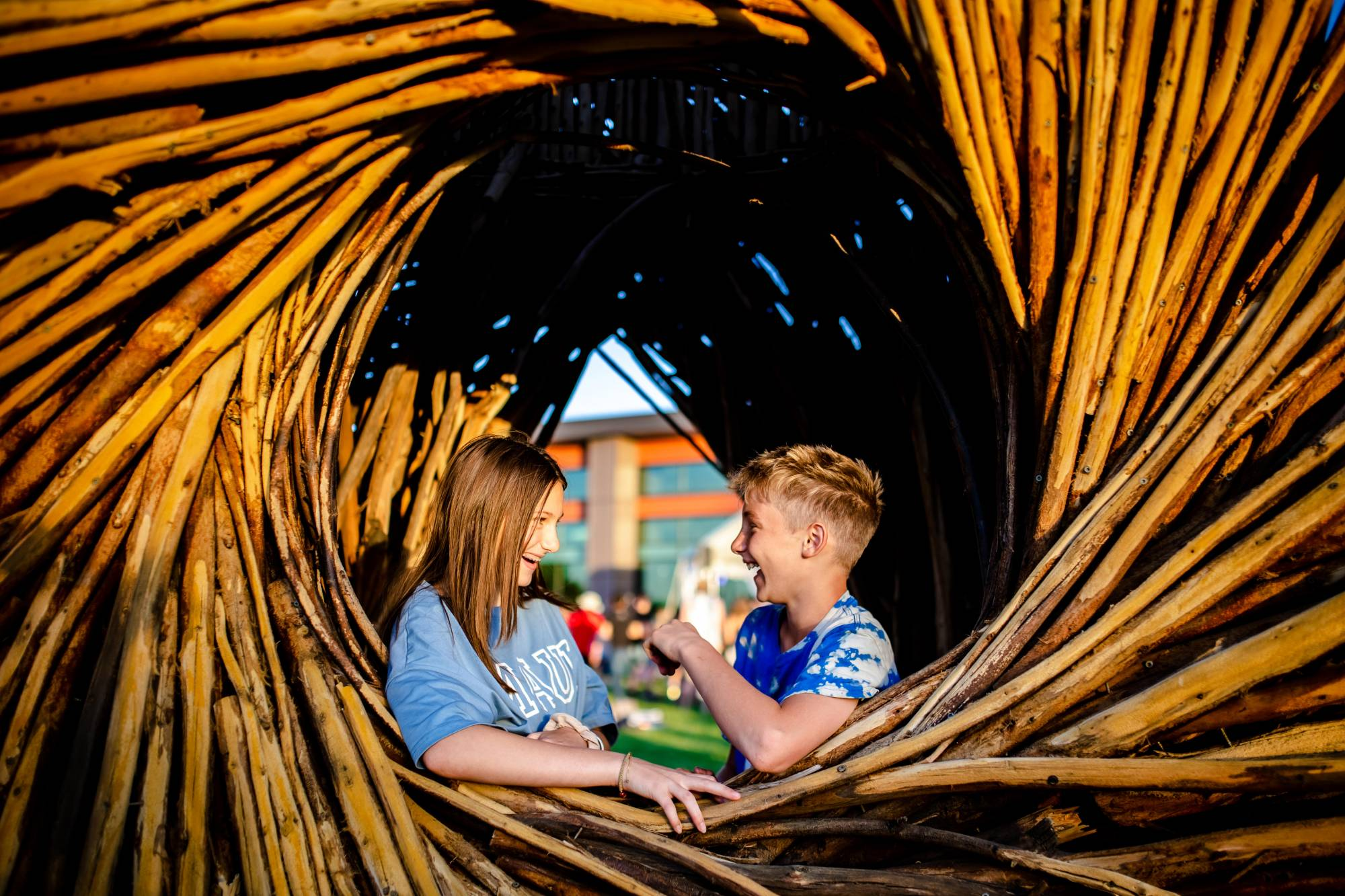 One teenage girl and one boy laugh while standing inside the Anythink Wright Farms wood spirit nest. They are both wearing blue short sleeve shirts.
