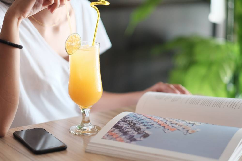 A photo of a woman sitting at a wood table and reading a large book with a orange cocktail and a iPhone in front of her. She is wearing a white t-shirt. The drink is in a tropical cocktail glass with a straw, swirled garnish and citrus fruit slice garnish.The photo shows her neck and torso.