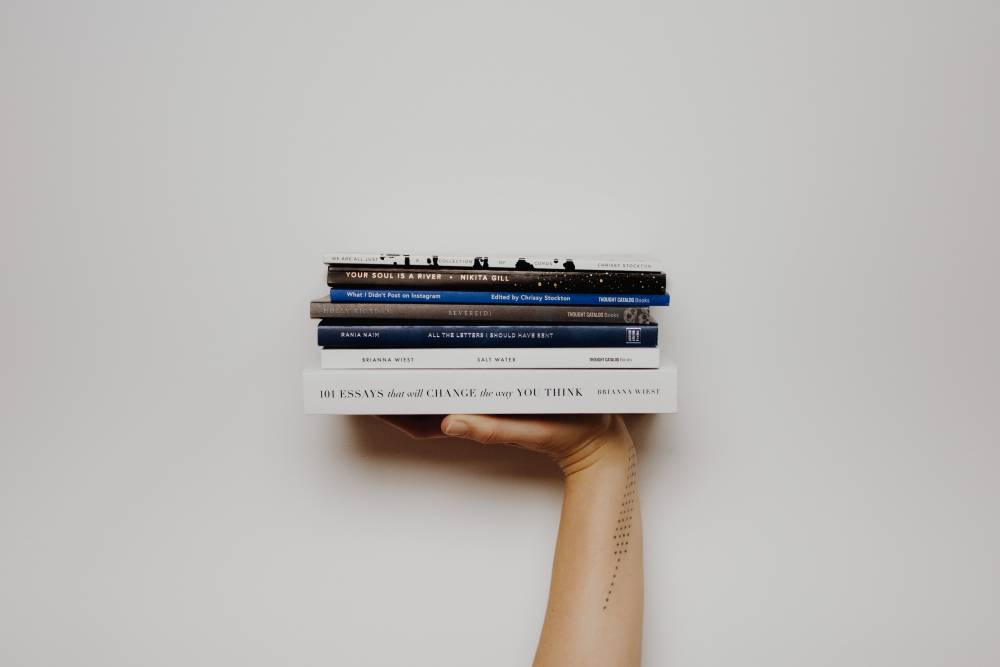 Photo of a person holding up a stack of books