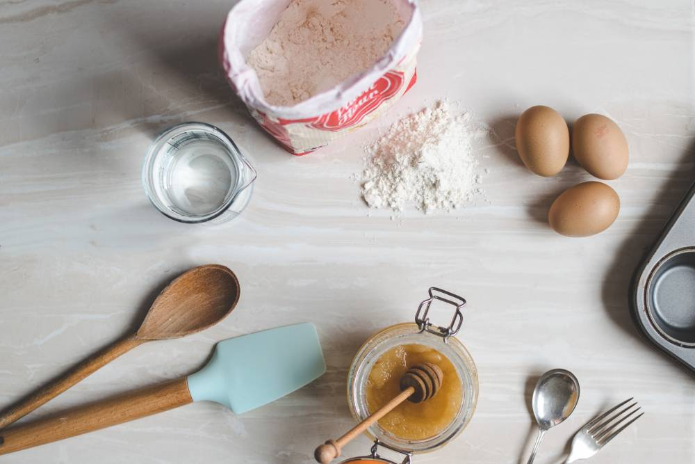 A kitchen table with baking supplies and ingredients