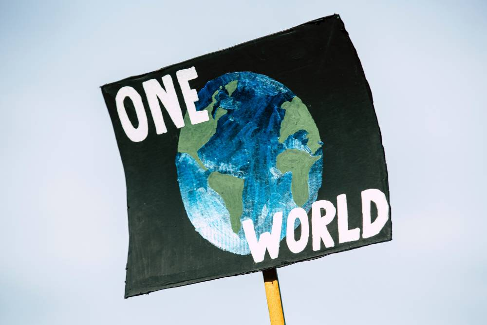 """A black poster against a blue sky with a blue and green painting of earth. Over the painting is white text that reads """"One World"""""""