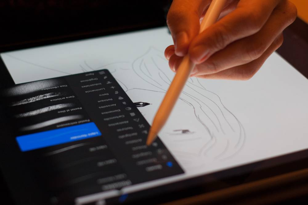 person drawing on digital tablet