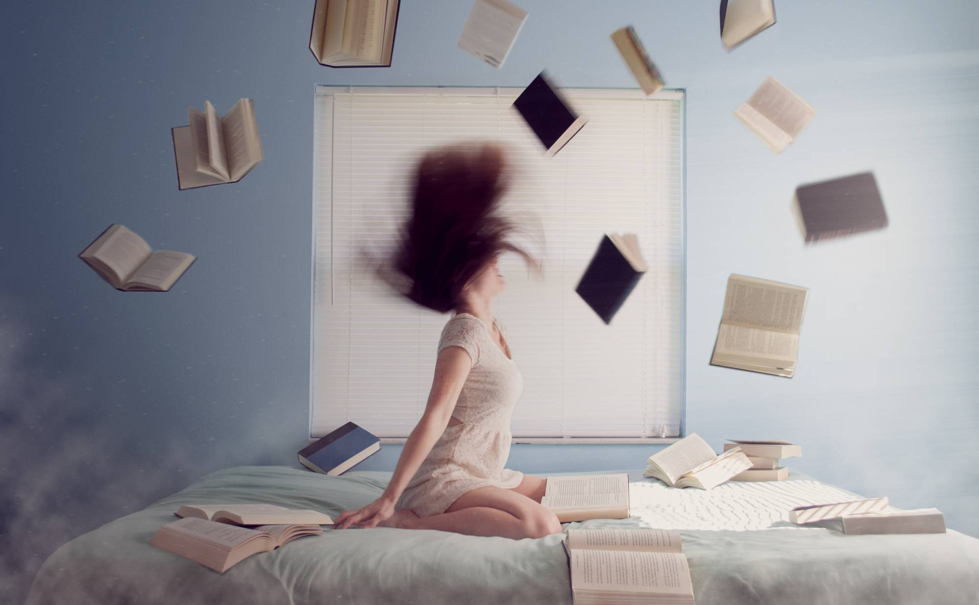 Photo of a woman in bed surrounded by books