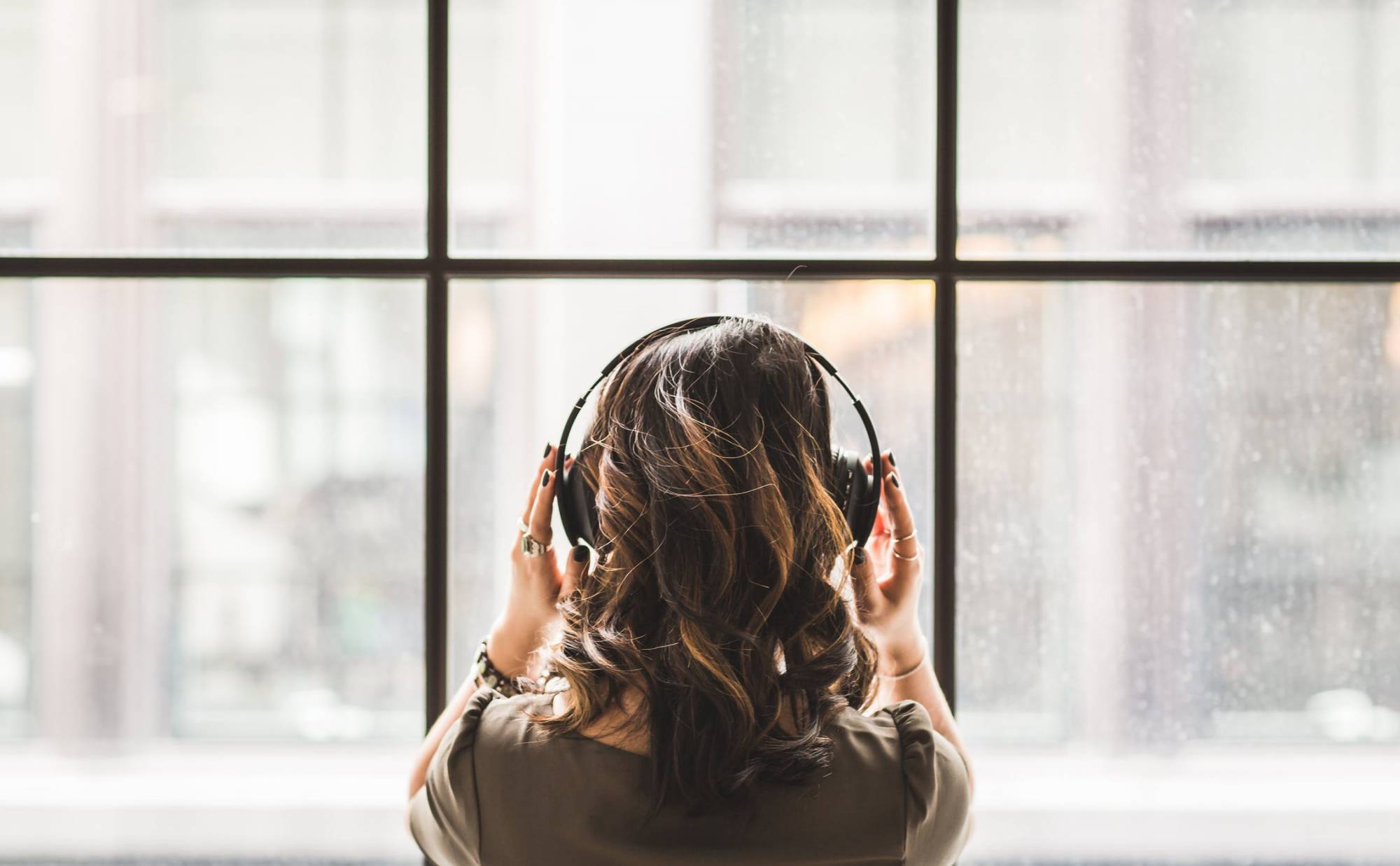 Photo of a woman staring out the window with headphones on