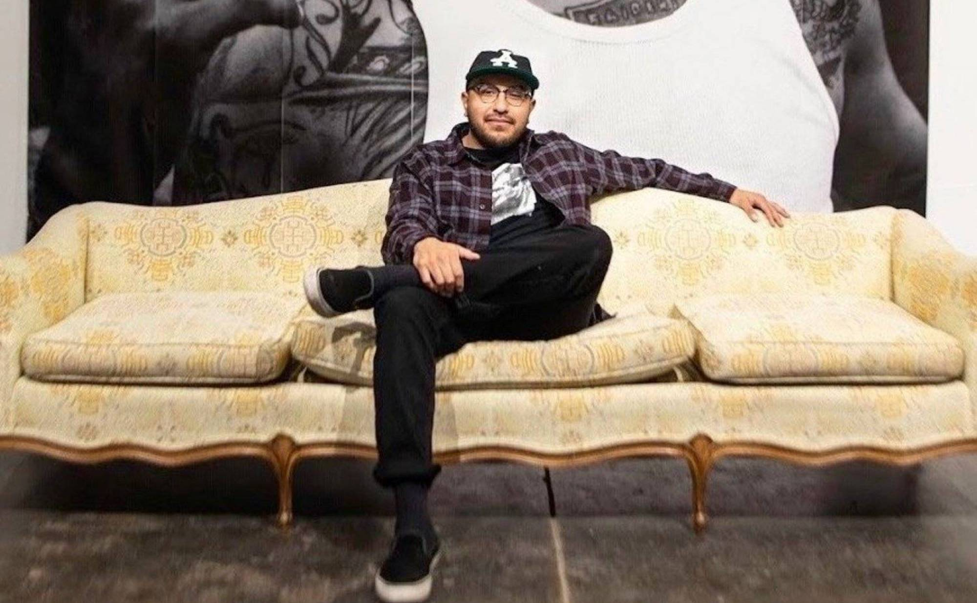 A photo of documentary photographer Juan Fuentes, sitting in the center of a yellow upholstered couch. There is a large-scale floor-to-ceiling black and white image on the wall behind him.