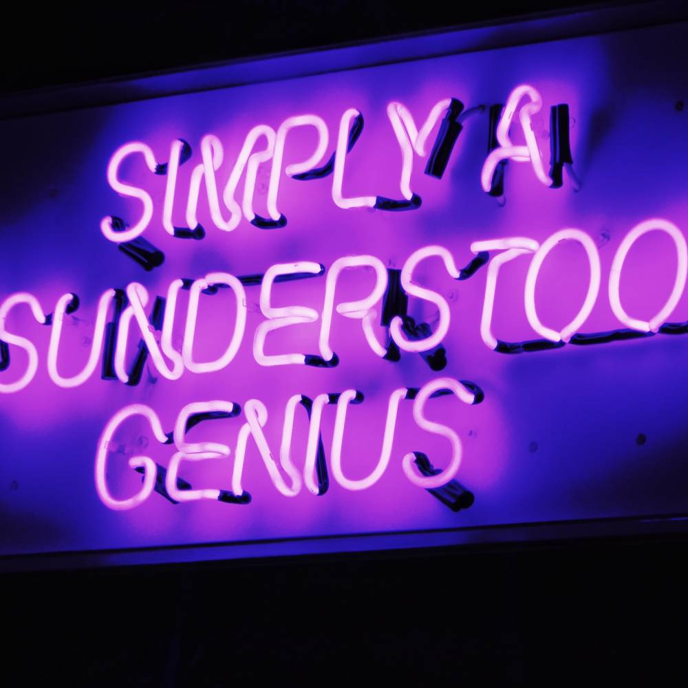 """A photo of a purple neon sign displaying text """"Simply A Misunderstood Genius"""""""