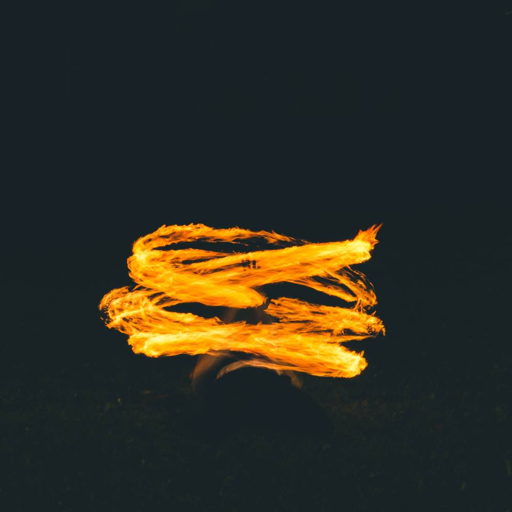 A artistic, flowing yellow, gold flame against a deep black background.