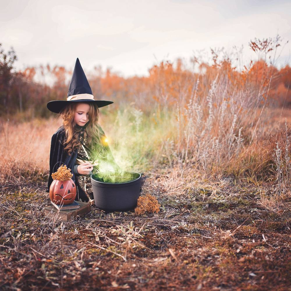 A girl dressed in a witch costume sitting by a black cauldron.