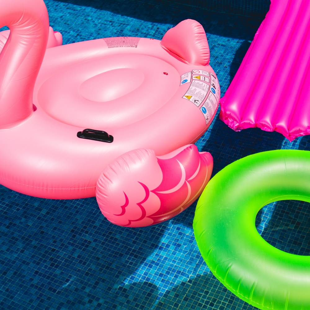 A photo of brightly colored pool floaties in a bright blue pool. Floaties include a pink flamingo, neon green inner tube, hot pink lounge floaty and aqua lounge floaty.